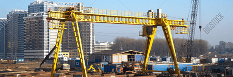 Large gantry crane and auto crane working at construction site